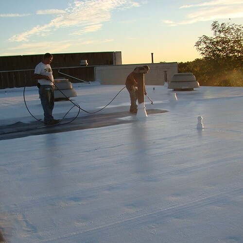 commercial roofer applying coating to roof